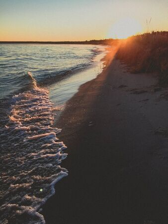 sun beam shining on the water at sunset Stock Photo