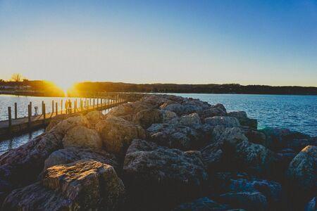 sunset over a rock jetty on lake michigan