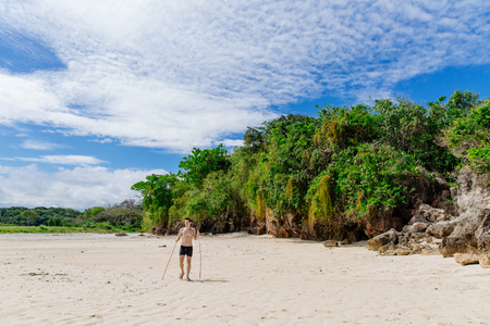 Man walking along the Coral Coast of Fiji at midday