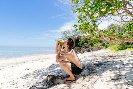 Man drinking coconut in the sunshine on the Coral Coast of Fiji