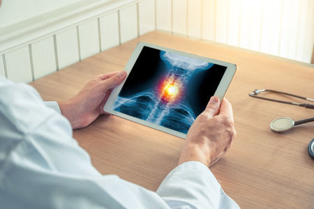 Doctor holding a x-ray of skeleton in medical office with stethoscope on the desk
