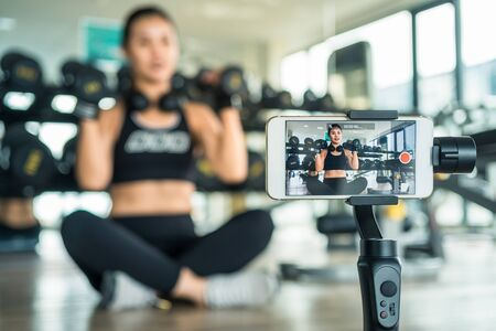 Woman teaching how to do fitness online with a smart phone. Stockfoto