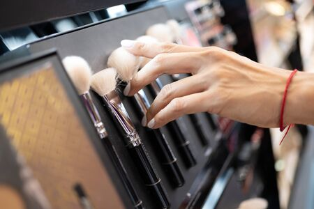 Hand of woman touching a cosmetic brush