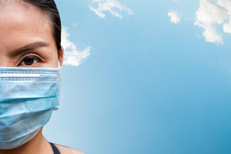 Asian woman wearing a mask against diseases and pollution with blank in blue sky