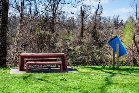 Picnic table and trash can at Riverfront Park in Wharton, Texas Stock Photo