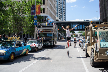 April 8, 2017, Houston, Texas: A man rides on a unicycle at the start line for the 30th Annual Art Car Parade Editorial