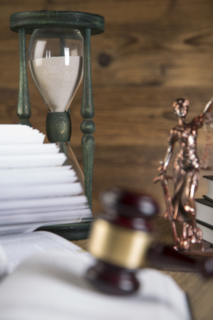 Lady of justice, hourglass, final speech, notebook, wooden   gold gavel and books on wooden table on brown wooden background Zdjęcie Seryjne
