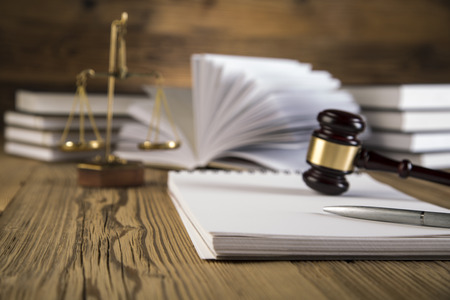 Golden scales of justice, wooden   gold gavel and books on wooden table on brown wooden  photo
