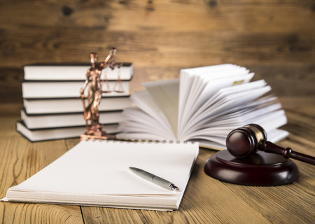 Lady of justice, final speech, notebook, wooden   gold gavel and books on wooden table on brown wooden