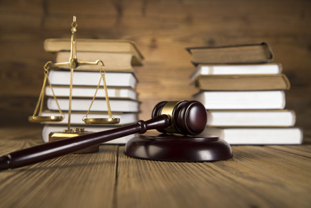 legal scales: Golden scales of justice, wooden   gold gavel and books on wooden table on brown wooden  Stock Photo