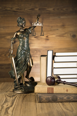 themis: Lady of justice, final speech, notebook, wooden   gold gavel and books on wooden table on brown wooden