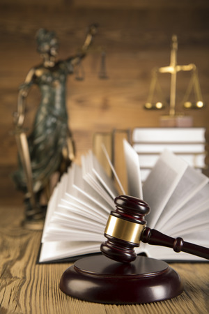 Lady of justice, final speech, notebook, wooden   gold gavel and books on wooden table on brown wooden  photo