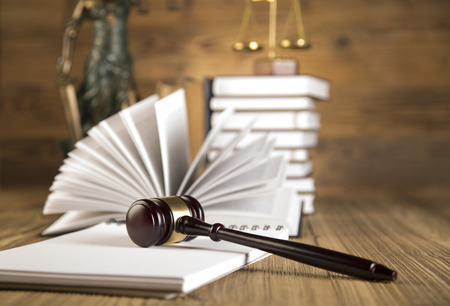 Lady of justice, final speech, notebook, wooden   gold gavel and books on wooden table on brown wooden background