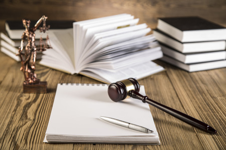 Goddess of justice, final speech, notebook, wooden   gold gavel and books on wooden table on brown wooden  photo