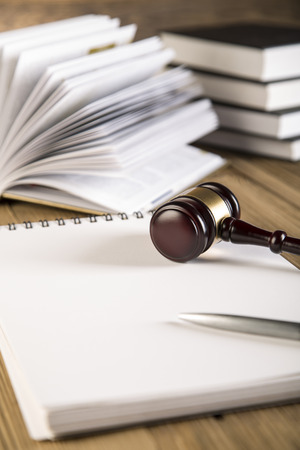 Notebook, final speech, wooden   gold gavel and books on wooden table on brown wooden  photo