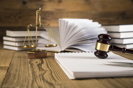 Golden scales of justice, final speech, wooden   gold gavel and books on wooden table on brown wooden background