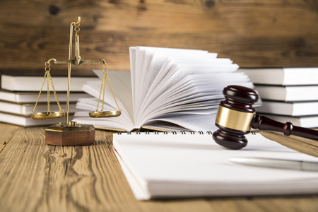 Golden scales of justice, final speech, wooden   gold gavel and books on wooden table on brown wooden