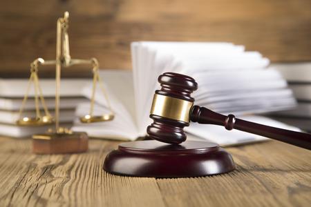 Zlaté váhy spravedlnosti, závěrečná řeč, dřevěné zlato palička a knihy o dřevěný stůl na hnědé dřevěné pozadí Reklamní fotografie