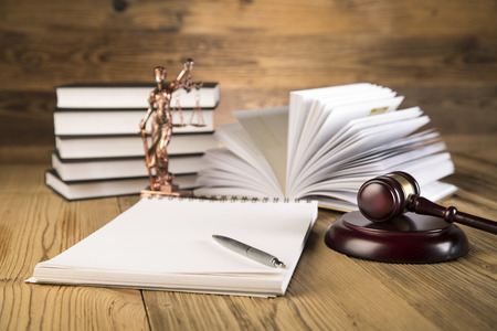 Lady of justice, final speech, notebook, wooden   gold gavel and books on wooden table on brown wooden Zdjęcie Seryjne - 28814136