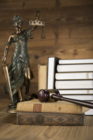 Lady of justice, final speech, notebook, wooden   gold gavel and books on wooden table on brown wooden Zdjęcie Seryjne - 28814086
