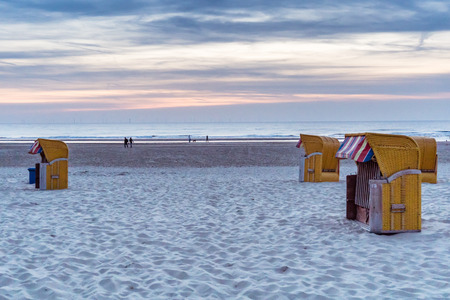 End of season... Yellow wicker and wood beach chairs stand quietly in the evening light on the nearly deserted beach at Egmond aan Zee., the Netherlands, North Holland Stock Photo