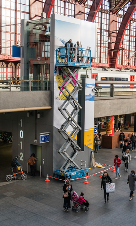 Antwerp, Belgium - 2018-10-01: Replacing a poster on the lift hoistway hig above the ground. Editorial