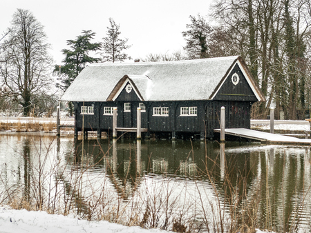 Breukelen, Netherlands - 2010-02-14: Wooden boathouse with thatched roof covered with a thin layer of snow, at the shore of River Vecht. Boathouse of Nijenrode rowing-club het Galjoen. Straatweg 60, 3621 BR Breukelen, Rijksmonument nummer: 520614