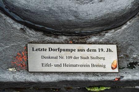 Metal plaque sign describing heritage village waterpomp