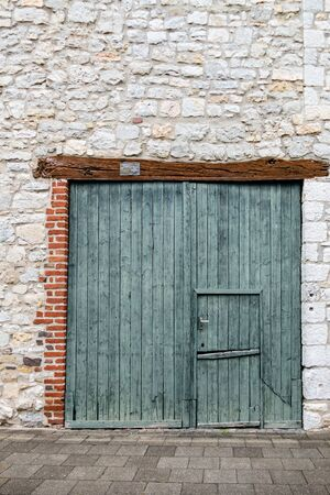 Old green double-hung barn door with wooden lintel. Editorial