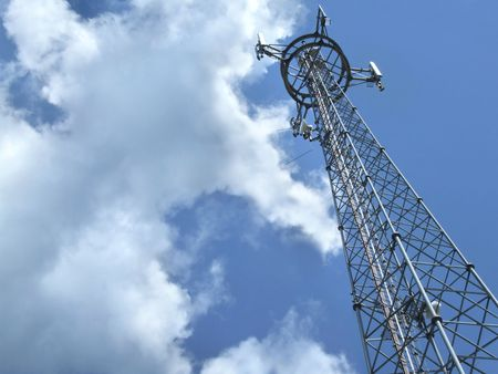 Telecommunication tower - antenna details against cloudy sky. Stock Photo