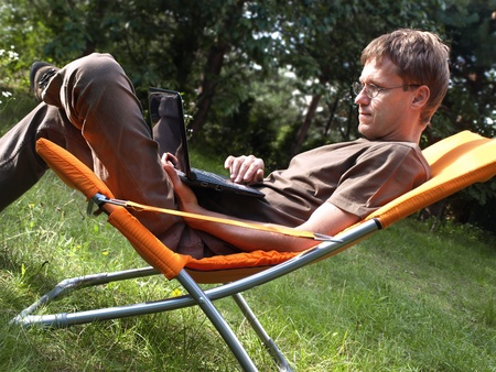 Young man in deckchair with netbook
