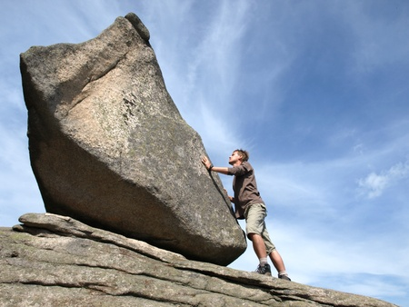 Determination - young man against the rock. Stock Photo