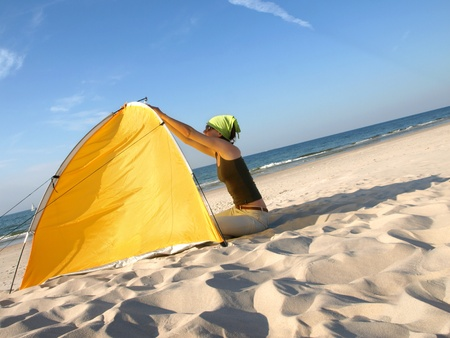 Young woman sitting at colorful beach tent. Stock Photo - 10797146