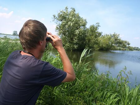 Birdwatching  - young man looking off through a binoculars in beautiful nature.