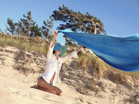 Happy young woman holding out beach towel