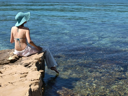 Woman sitting on the shore of Adriatic sea.