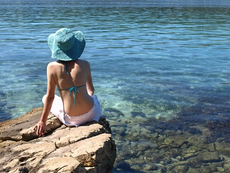 Woman sitting on the shore of Adriatic sea. Croatia