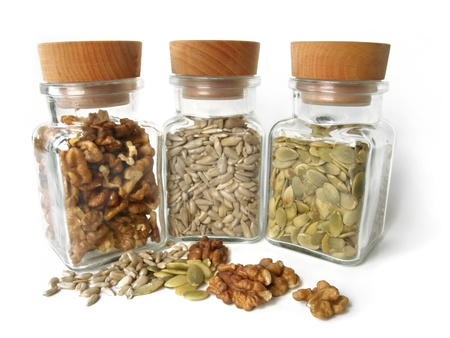 healthy seeds - sunflower seeds, pepita and walnut in a glass bottles