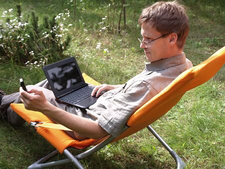 netbook: Young man with netbook and cell phone in hand Stock Photo