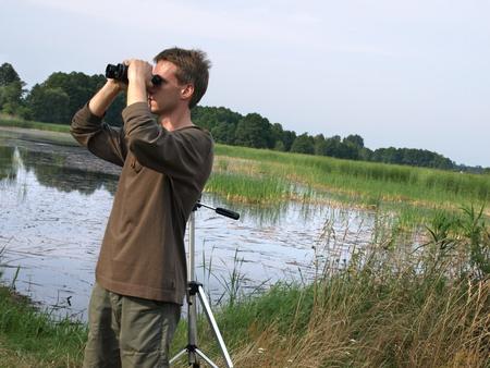 birdwatcher: Young man looking off through a binoculars in beautiful nature  Stock Photo