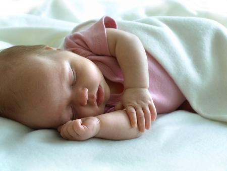 0 1 months:  Four week old newborn girl sleeping on white blanket