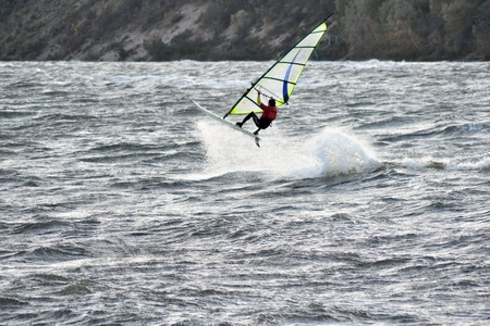 Dynamic shot of windsurfer jumping on stormy waves of Baltic sea.