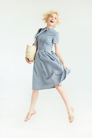 checkroom: Blonde happy girl in a blue dress with a bag on a white background