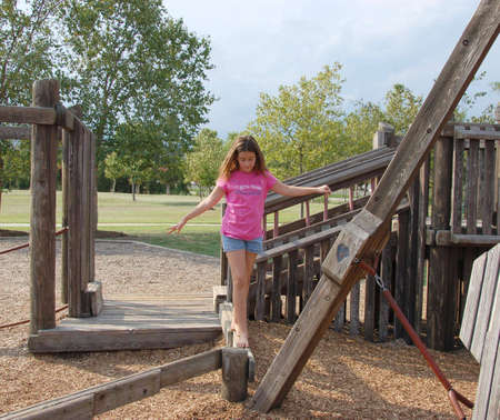 Girl walking on a balance beam in a playground