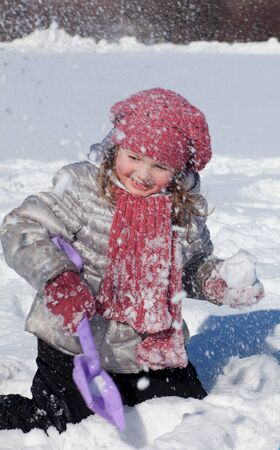 The girl in pink cap and scarf plays with a shovel on snow photo