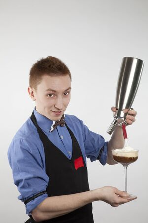 The young barman fills a glass with a cream from a creamer photo