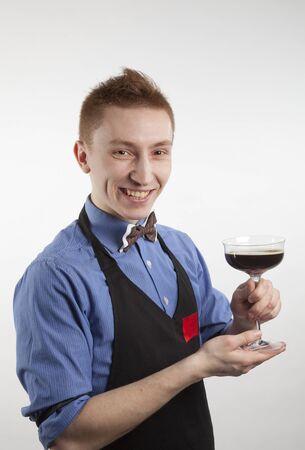 The smiling barman keeps a glass