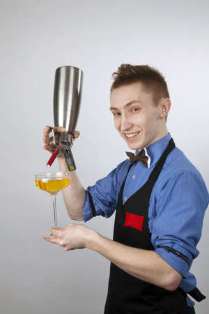 The young barman fills a glass with a cream from a creamer