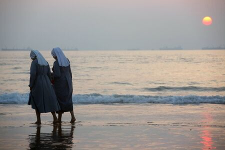 Two catholic nuns walk by a sea coast during sunse