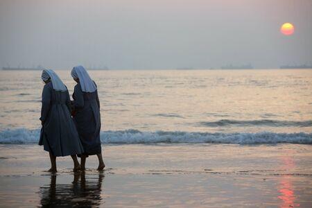 Two catholic nuns walk by a sea coast during sunse photo